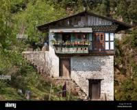 A traditional stone Bhutanese house built on a hillside ...
