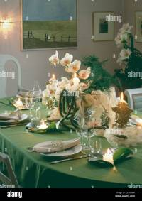 Christmas table setting with green table cloth, flower ...