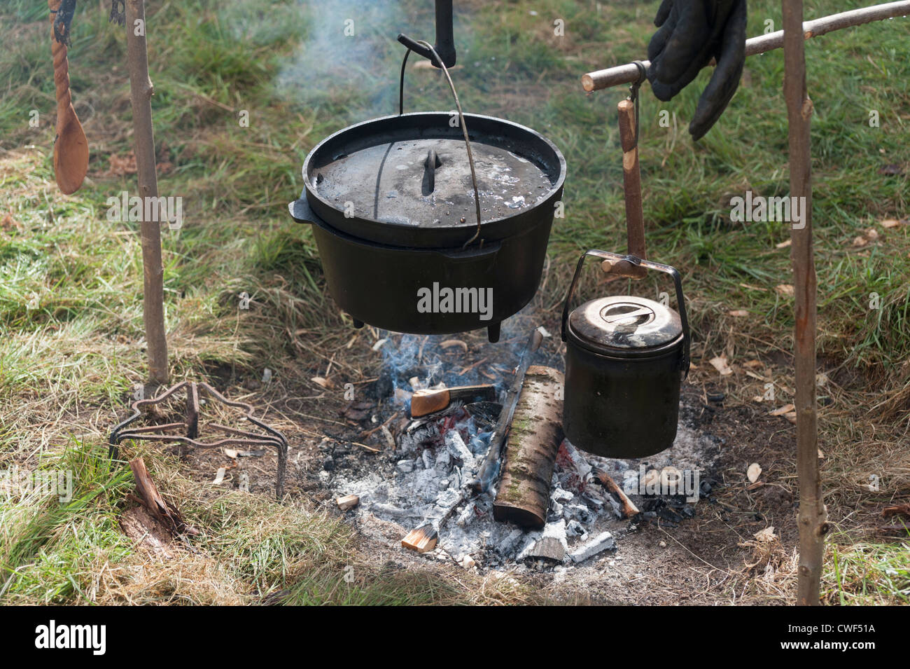 Cast Iron Pot Campfire With Cast Iron Pots And Pans Hanging Over A Wood