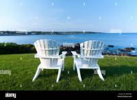 Two white Adirondack chairs on a lawn overlooking the ...