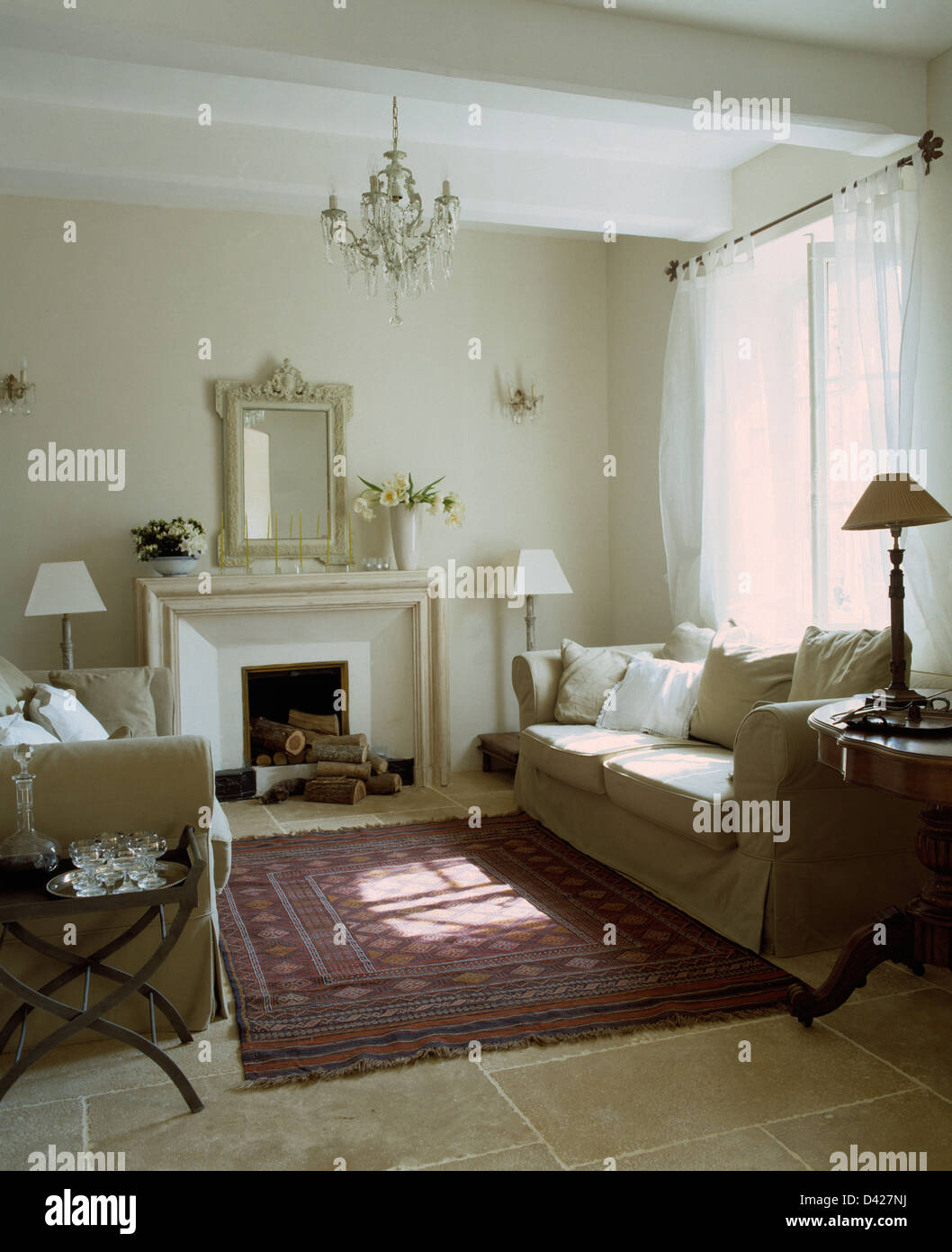 Cream sofas on either side of fireplace in French country