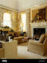 Beige sofas and cream carpet in yellow country living room ...