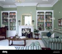 Fitted white bookcases on either side of fireplace in gray ...