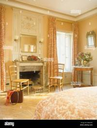 Antique chairs on either side of fireplace in bedroom of ...