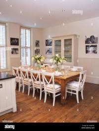 White chairs at simple wood table in modern white kitchen ...
