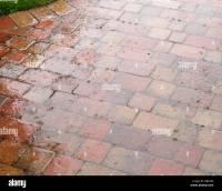 Heavy raindrops splashing on Rustic red brick patio paving ...