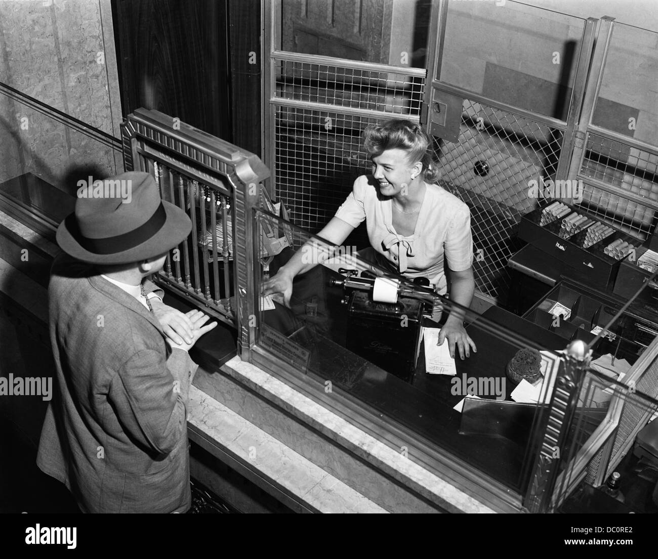 Banc Tele 1940s Woman Bank Teller Behind Cage Serving Male Customer