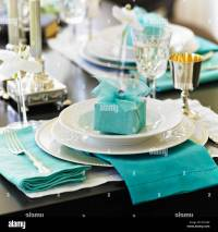 Formal table setting with white dishes and blue gift and ...