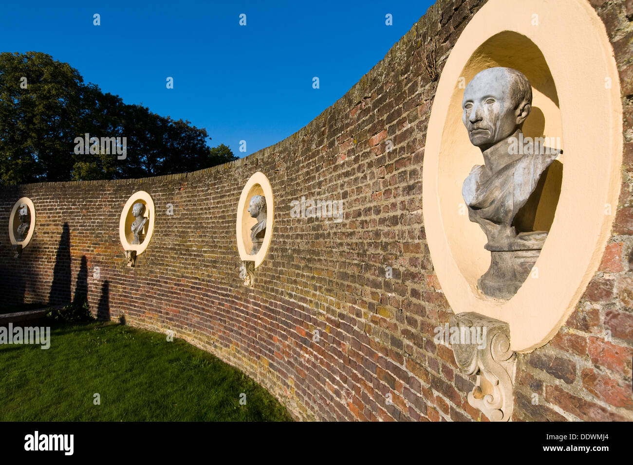 Line of decorative ornamental bust busts statue statues on display in the front garden wall walls of ham house surrey uk