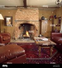 Lighted fire in exposed brick fireplace in neutral country ...