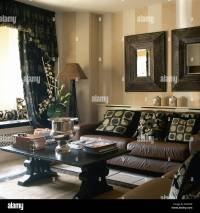 Heavy wood framed mirrors above brown leather sofa with ...