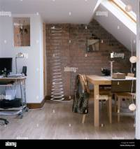 Pale wood table and chairs in dining area of small loft ...