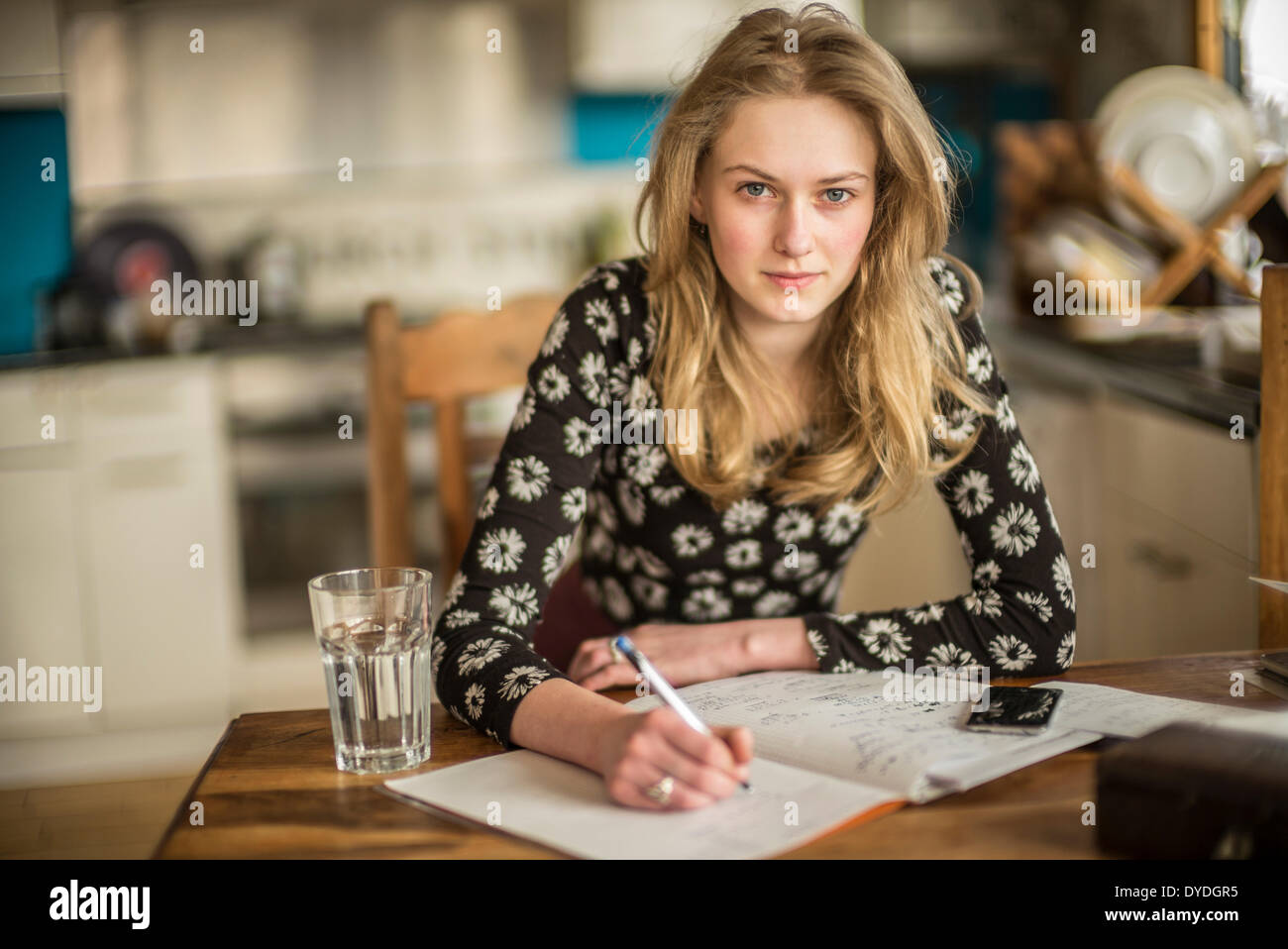 a 16 year old girl doing math homework on the kitchen table DYDGR5