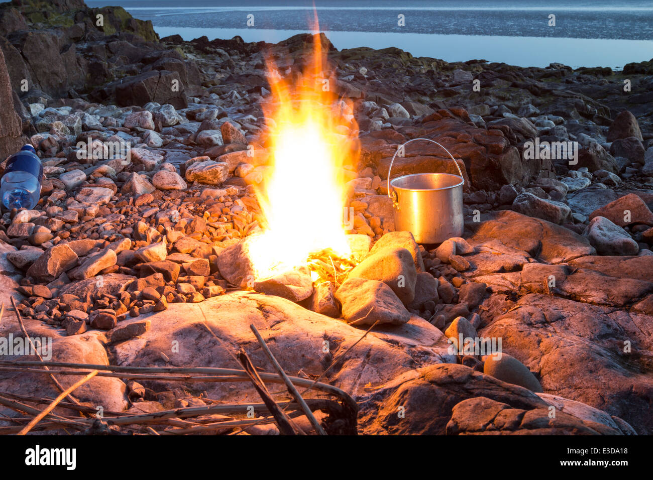 Camp Fire With Cooking Pot On A Rocky Beach At Dusk