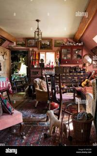 Cluttered cottage living room full of antique furniuture ...