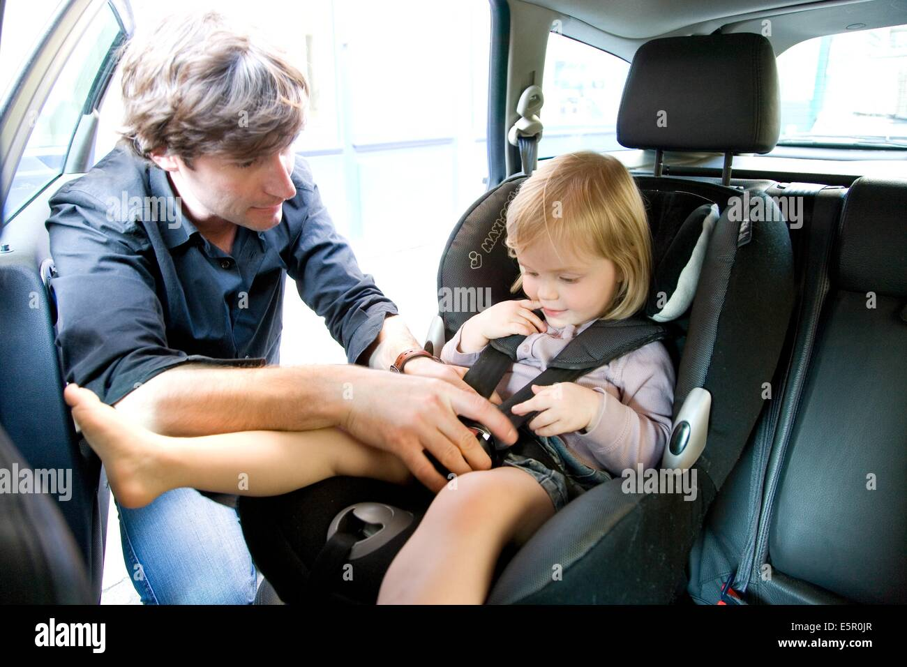 Father Securing His 2 Year Old Baby Girl In A Baby Car