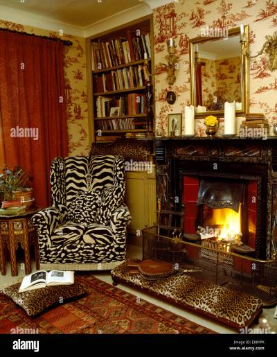 Tiger print wing chair and leopard print stool beside fireplace in Stock Photo, Royalty Free ...