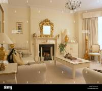 Cream living room with cream table and sofas and gold ...