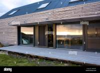 Exterior of modern wooden house with decked terrace and ...