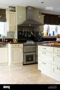 Cream travertine floor tiles in modern kitchen with large ...