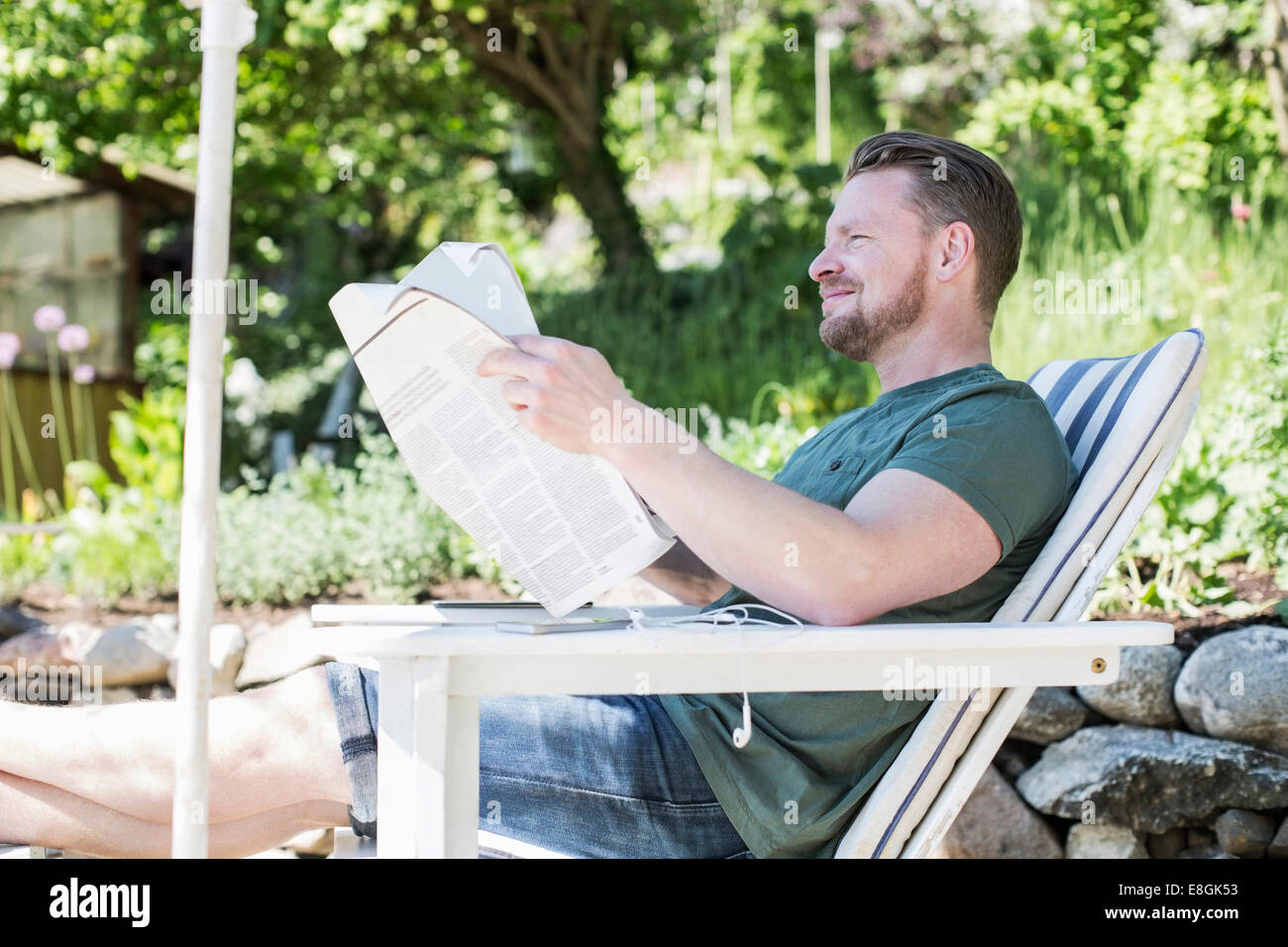 Outdoor Reading Chair Side View Of Smiling Man Reading Newspaper On Lounge Chair