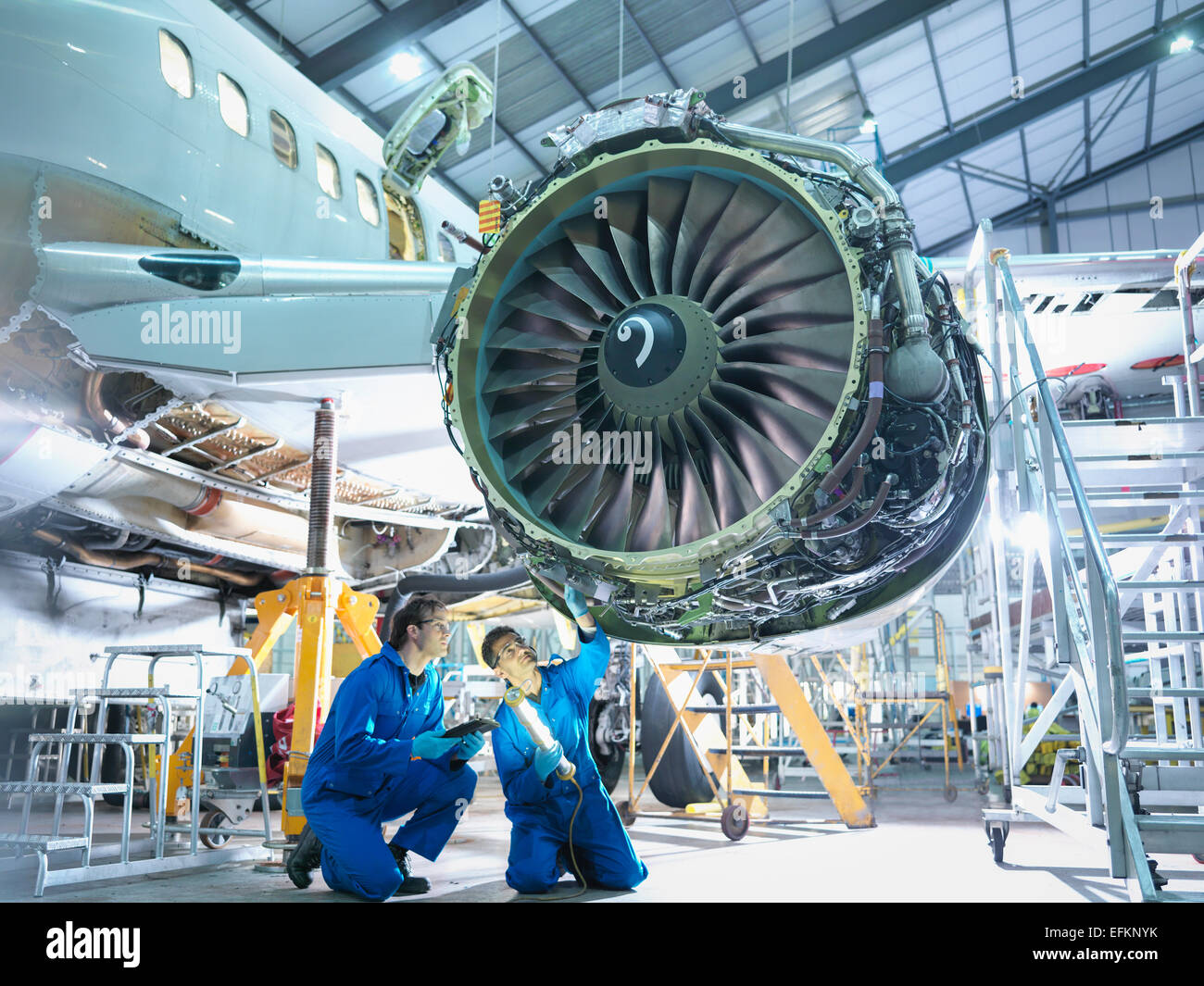 Airplane Maintenance Aircraft Engineers Inspecting Jet Engine In Aircraft Maintenance
