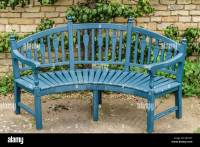 Blue wooden garden bench seat in front of old stone wall ...