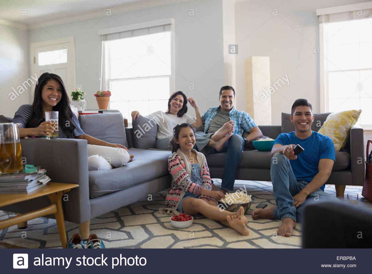 Family watching TV with popcorn in living room Stock Photo