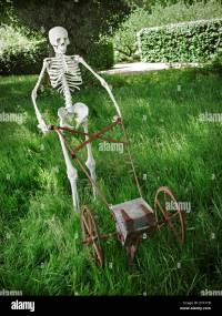 Quirky sculpture of skeleton mowing grass in an overgrown ...