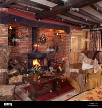 Wood burning stove in inglenook fireplace in a beamed ...