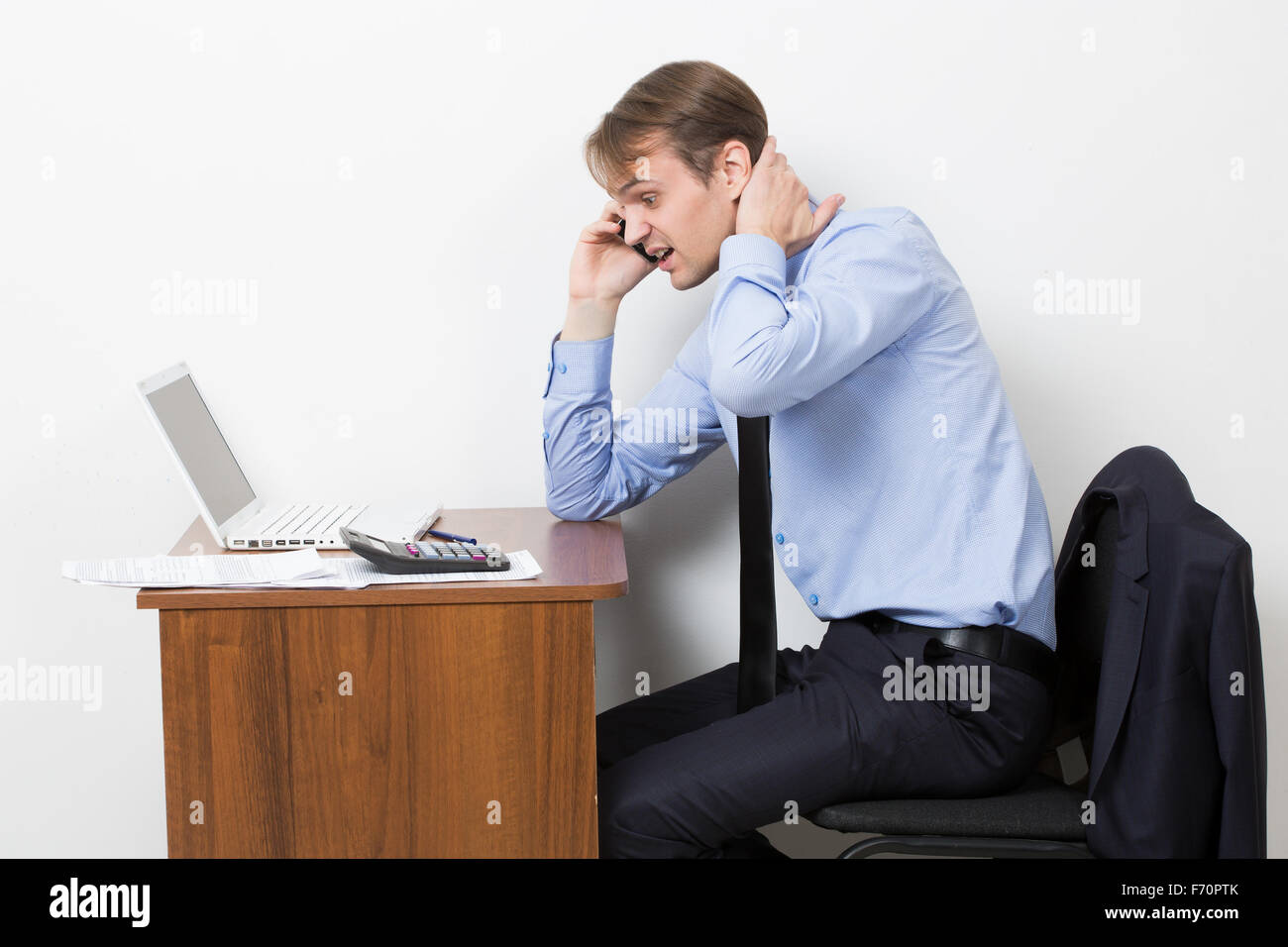 Stock photo frustrated office worker on the phone holding neck