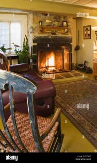 Antique rocking chair and leather sofa with lit fireplace ...