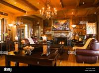 Lit stone fireplace and brown leather chairs and sofas in ...
