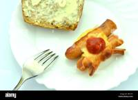 grilled sausage in cheese on a plate isolated on white ...