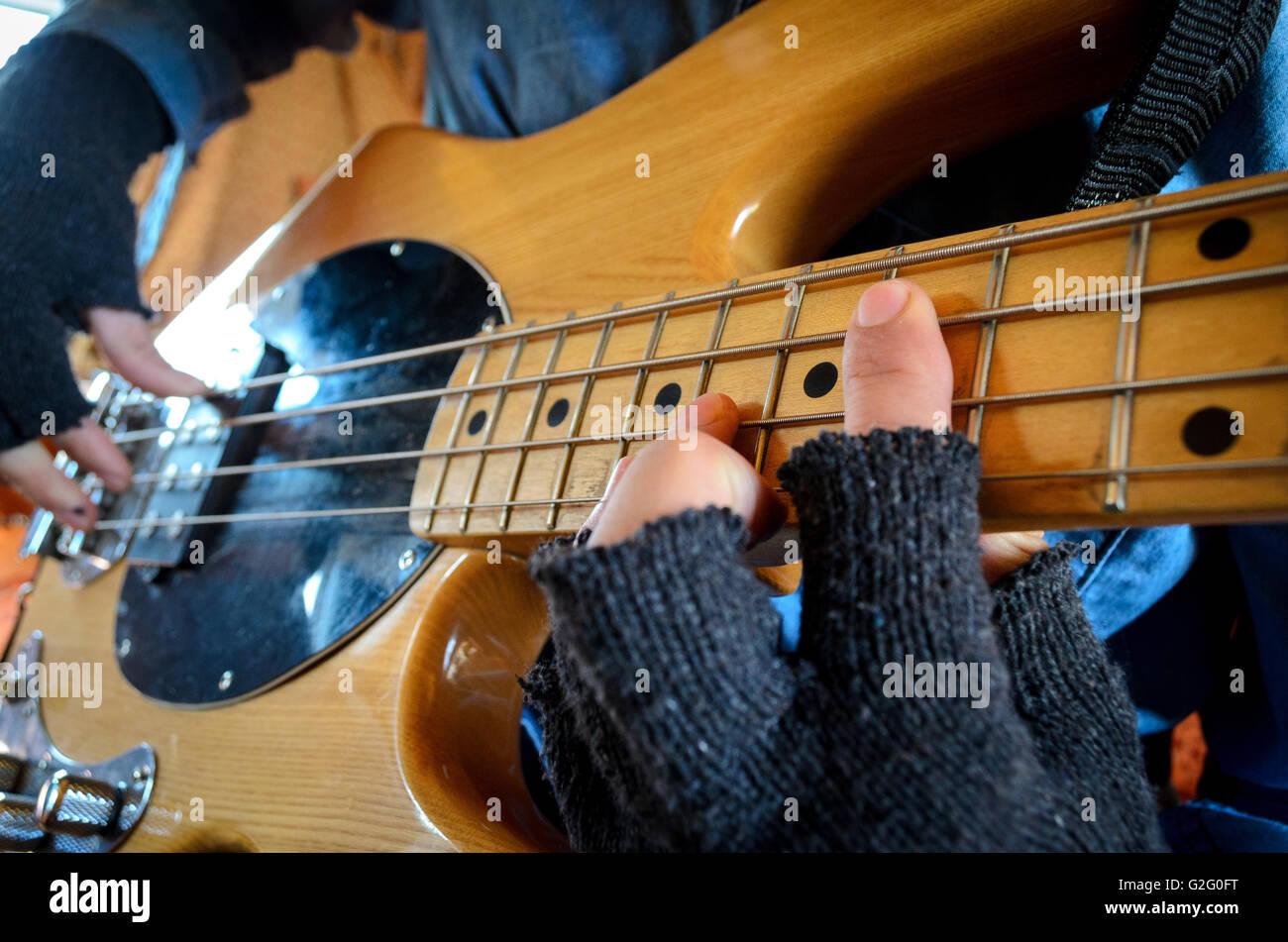 Playing bass guitar wearing fingerless gloves