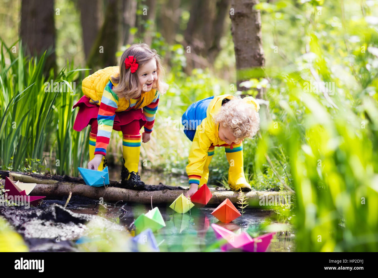 Baby Toddler Rain Boots Children Play With Colorful Paper Boats In A Small River