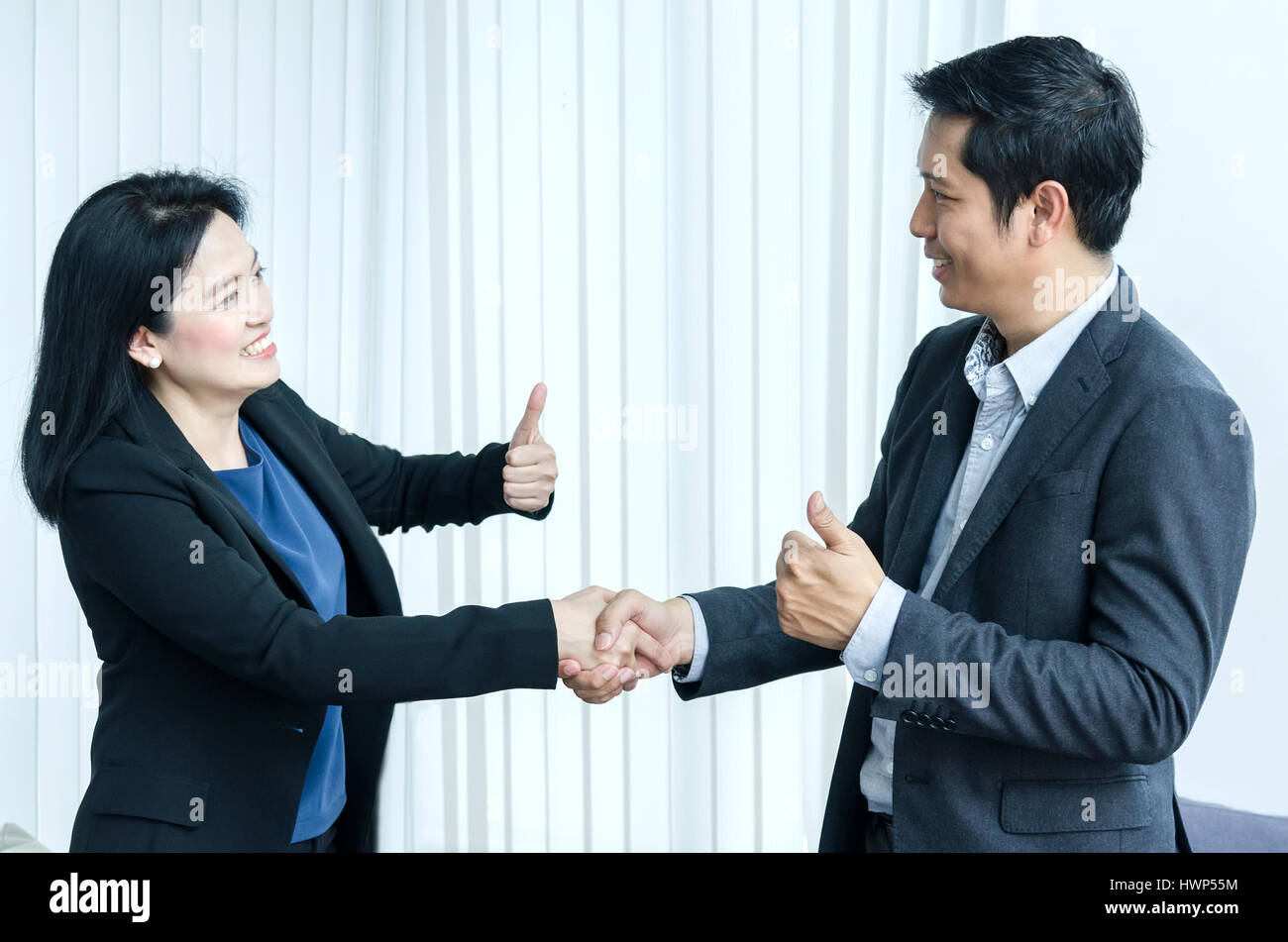 Success business team concept asian woman and man handshake and showing thumbs up