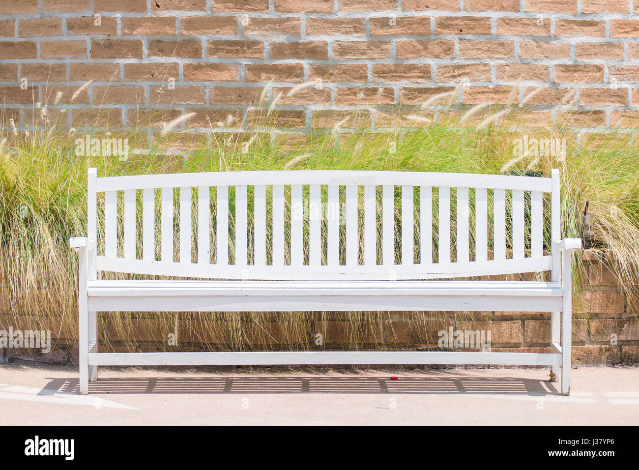 White long chair against a background of grass and brick wall Stock Photo - Alamy