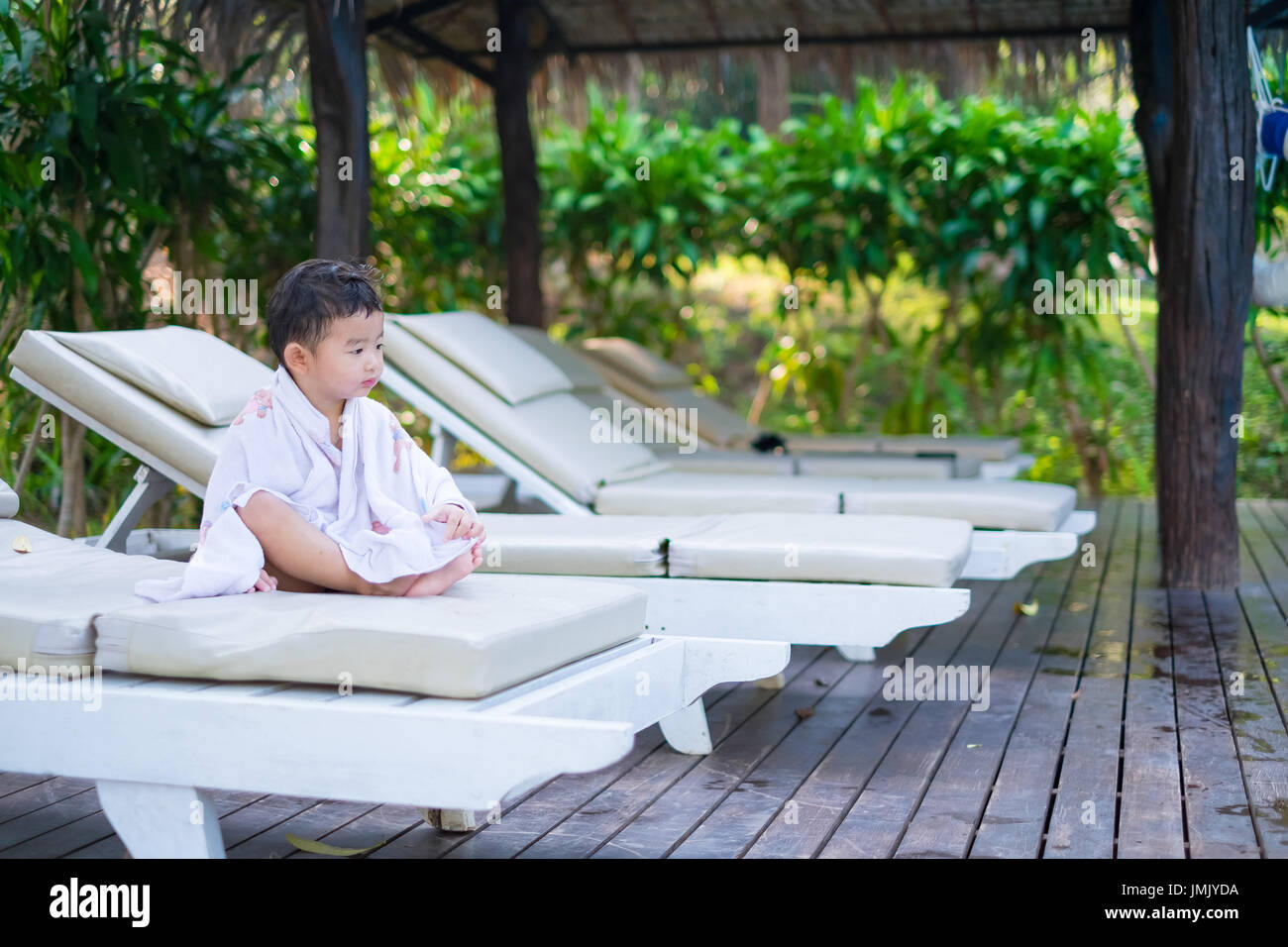 White Sun Lounge Asian Boy With White Towel Resting On A Lounge Deck Chair Or Sun