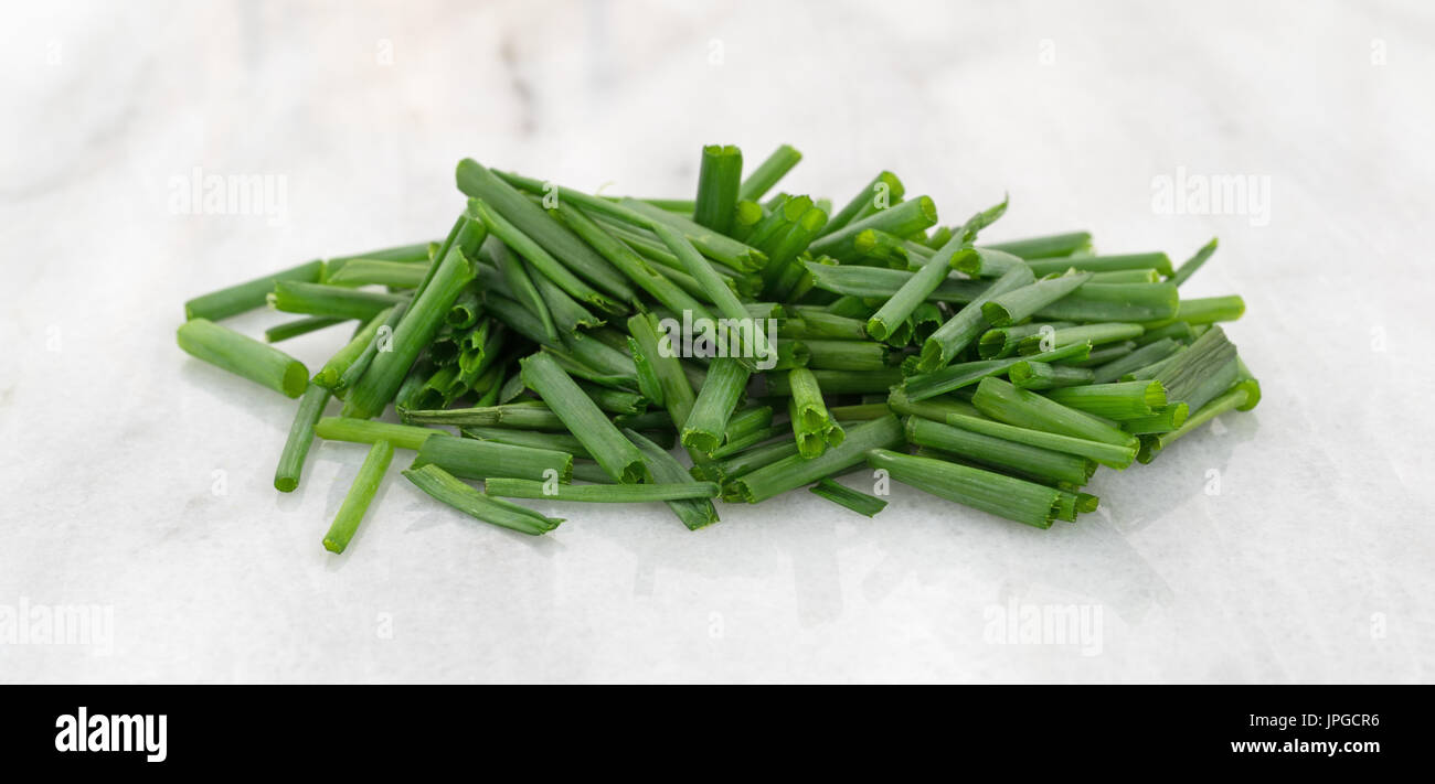 Small Marble Cutting Board Cut Organic Chives In A Small Pile Atop A Gray Marble Cutting