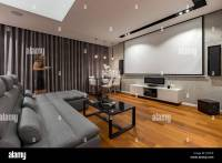 Living room with projector screen, gray couch and black ...