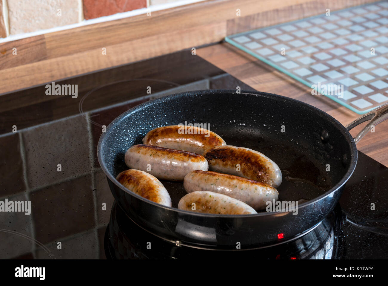 Cuisine Induction Sausages Cooking In A Frying Pan On An Induction Hob Stock Photo