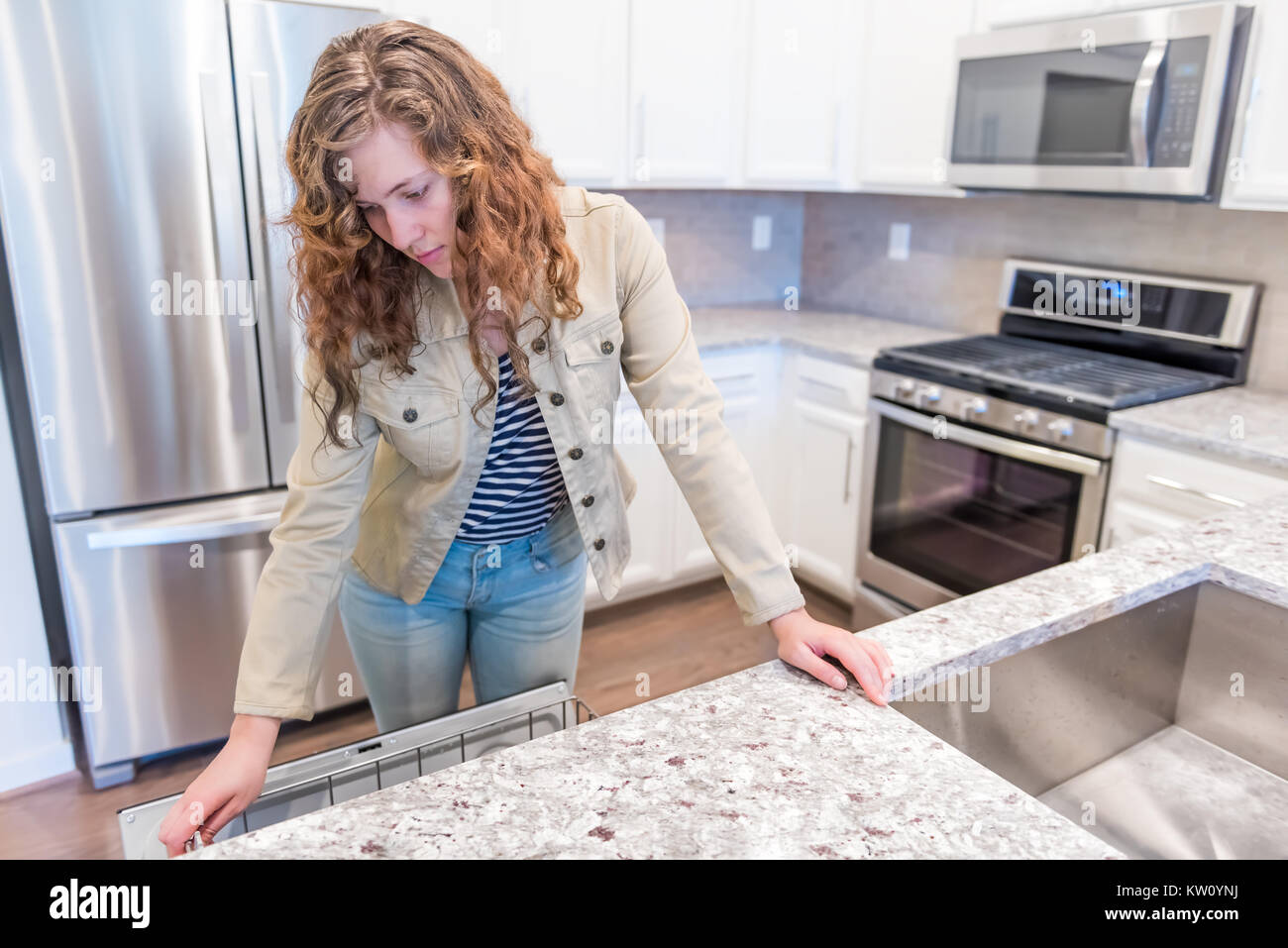 Gray Brown Backsplash Young Woman Opening Inspecting Dishwasher In Modern Gray Brown