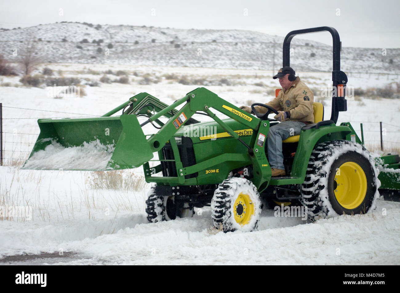 John Deere Snow Plow A Farmer Plowing Snow With A John Deere Tractor Stock Photo
