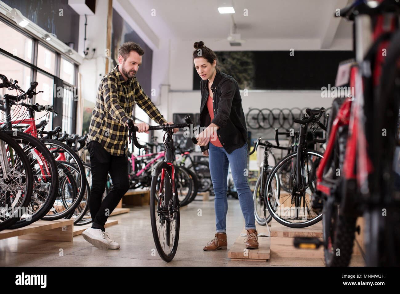 A Bike Store Small Business Owner Serving Customer In A Bike Store Stock Photo