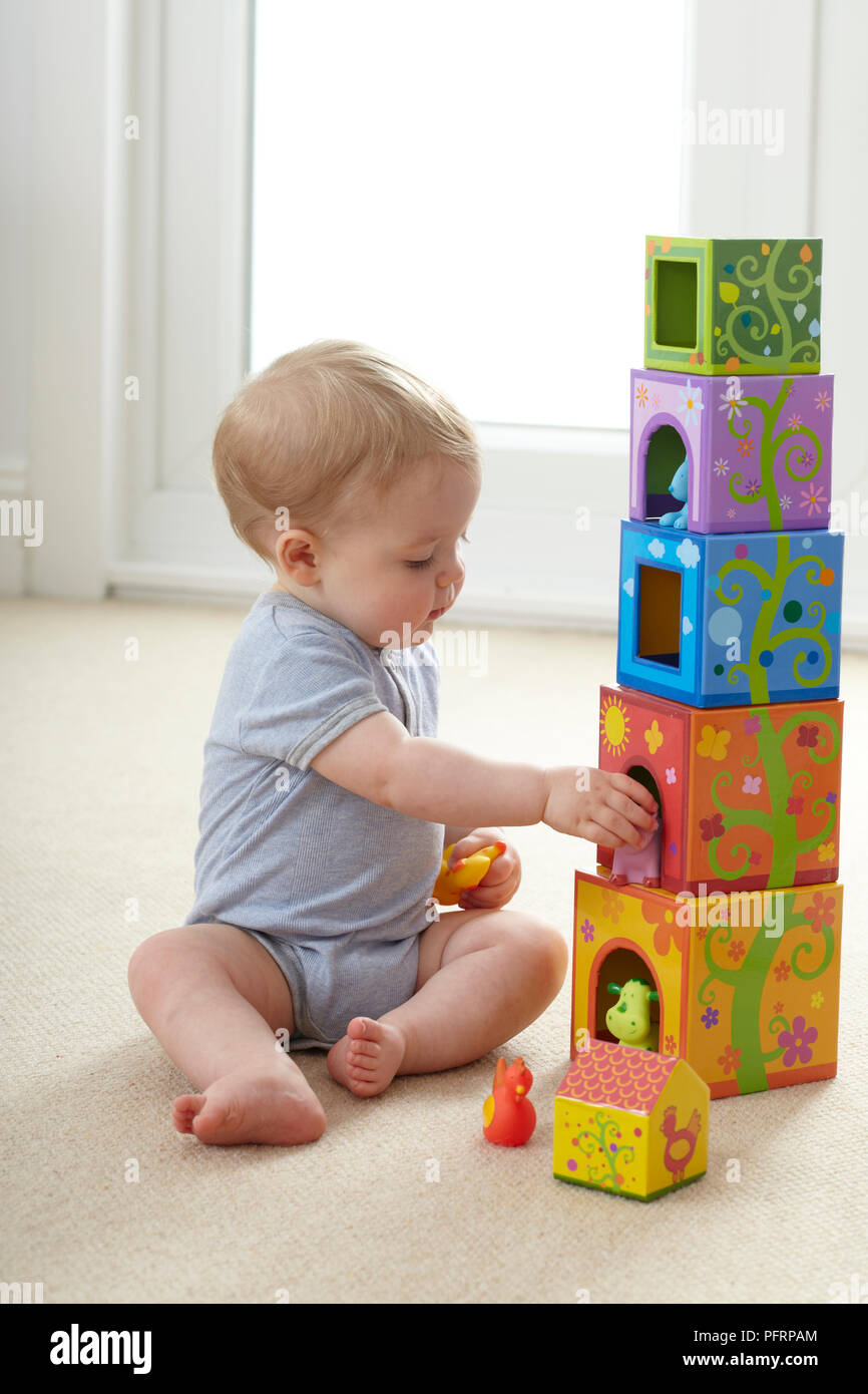 Baby Boy 12 Months Sitting On Floor And Playing With Stack Toys Stock Photo Alamy