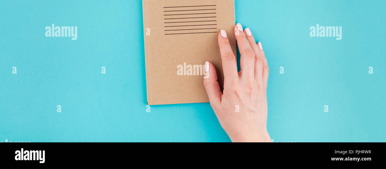 Long wide banner of woman hands holding craft paper notebook diary