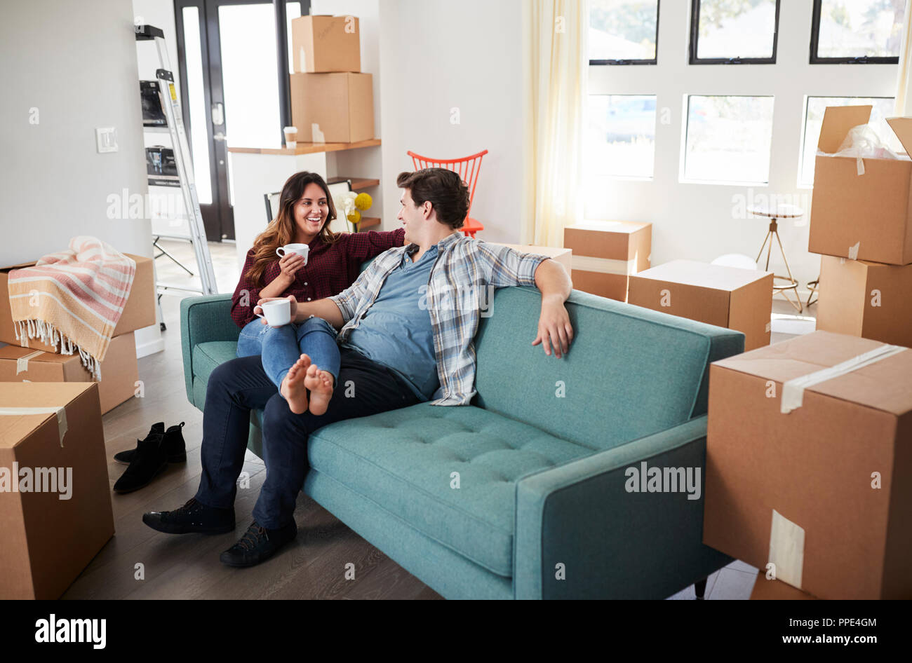 Home Sofa In A Box Happy Couple Resting On Sofa Surrounded By Boxes In New Home On