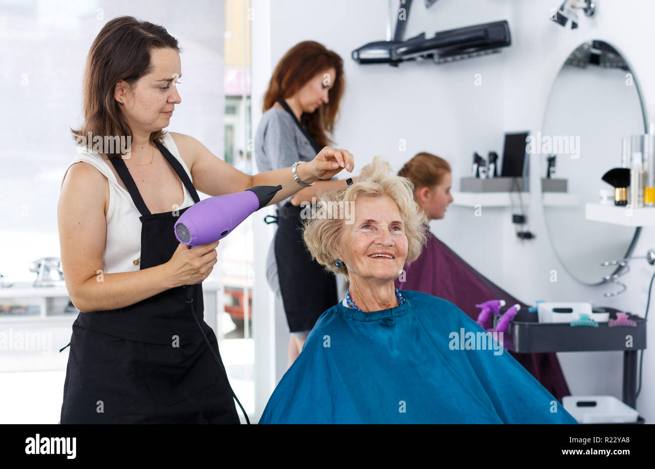 Salon Senior Professional Female Stylist Making Hairdo For Senior Woman