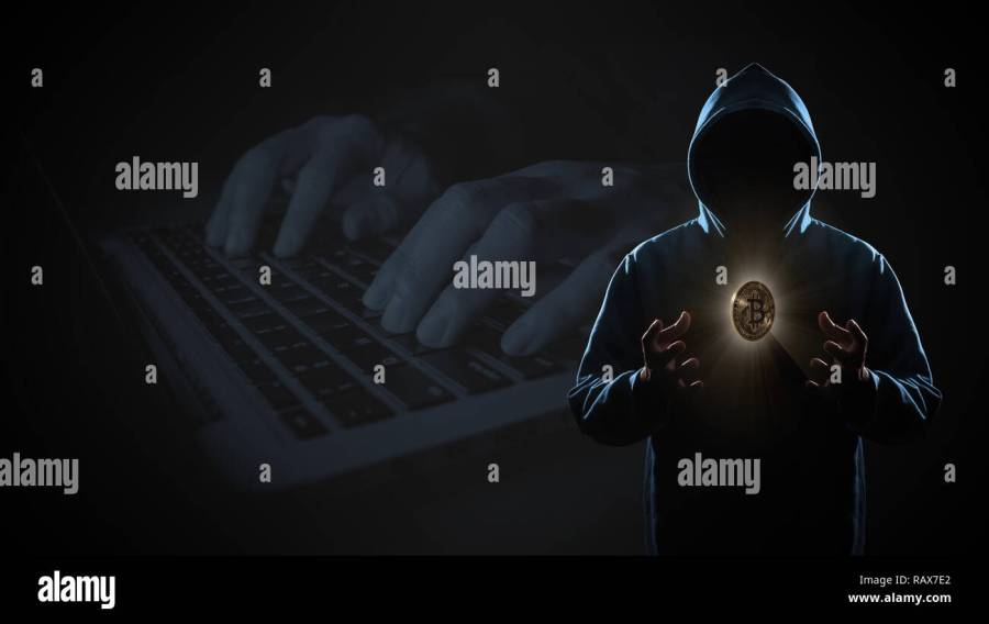 Golden Bitcoin floating above of hacker\u0027s hand in dark on hacker hacking with computer laptop background with copy space. Finance, business, e-commerc